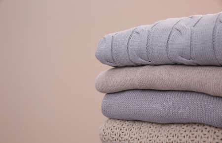 Stack of folded warm sweaters on gray background, closeup. Space for text