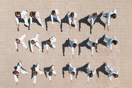 OCHAKIV, UKRAINE - JULY 09, 2020: Children in kimono practicing karate outdoors, aerial top view. Spending time in summer camp