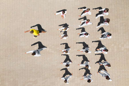 OCHAKIV, UKRAINE - JULY 09, 2020: Children practicing karate with coaches outdoors, aerial top view. Spending time in summer camp