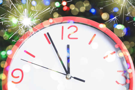 Clock showing five minutes till midnight with sparklers, closeup with bokeh effect. New year countdown