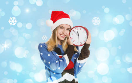 New Year countdown. Happy woman in Santa hat holding clock on light blue background