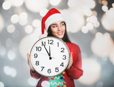 New Year countdown. Happy woman in Santa hat holding clock against blurred lights on background