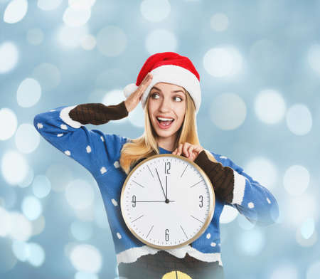 New Year countdown. Excited woman in Santa hat holding clock on light blue background