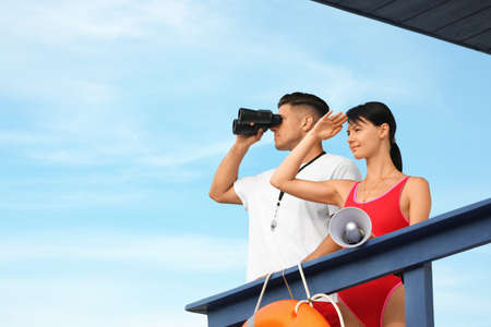 Lifeguards with megaphone and binocular on watch tower against blue sky