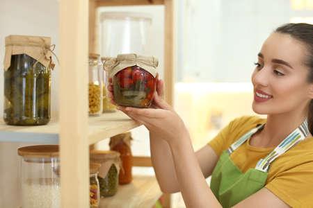 Woman putting jar of pickled vegetables on shelf indoors