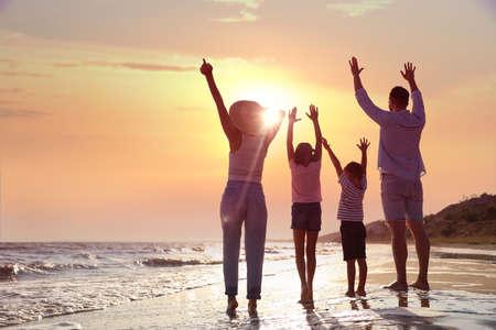 Family on sandy beach near sea. Summer vacation
