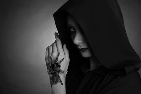 Mysterious witch with spooky spider on dark background, space for text. Black and white effect