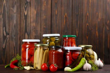 Jars of pickled vegetables on wooden table Foto de archivo
