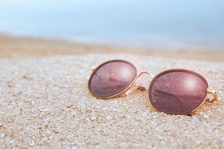 Stylish sunglasses on sandy beach near sea
