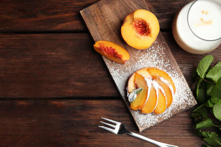 Delicious peach dessert on wooden table, flat lay. Space for text Reklamní fotografie