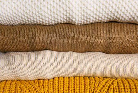 Stack of folded knitted sweaters as background, closeup