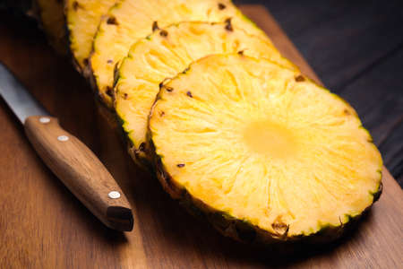 Tasty cut pineapple and knife on wooden board, closeup