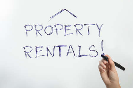 Woman writing exclamation mark in phrase Property Rentals on glass, closeup Imagens