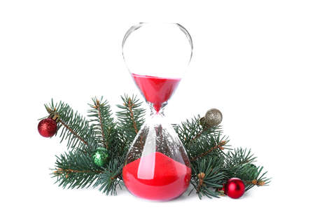 Hourglass, fir tree twigs and decor on white background. Christmas countdown Foto de archivo
