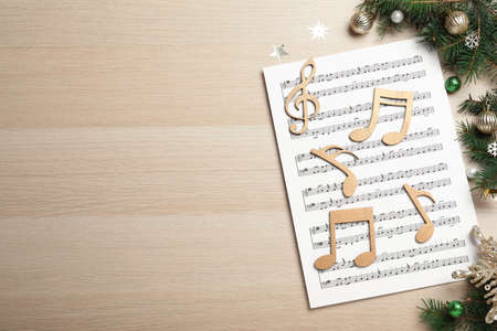 Flat lay composition with Christmas music sheets on wooden background. Space for text
