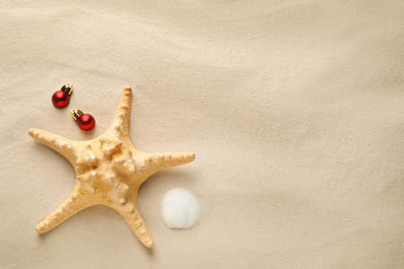 Beautiful starfish, shell, festive balls and space for text on sand, flat lay. Christmas vacation