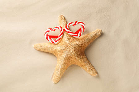 Beautiful starfish with candy cane party sunglasses on sand, top view. Christmas vacation