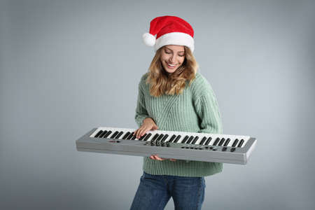 Young woman in Santa hat playing synthesizer on light gray background. Christmas music