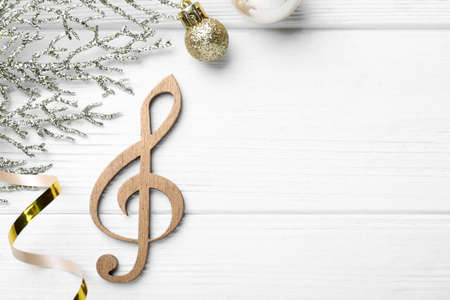 Flat lay composition with music note on white wooden background, space for text. Christmas celebration