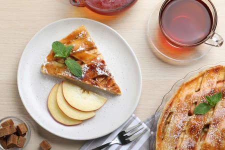 Slice of traditional apple pie served on wooden table, flat lay