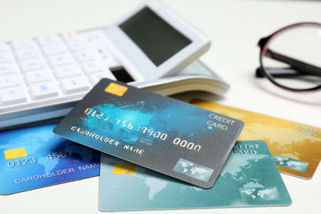 Credit cards and calculator on white table, closeup