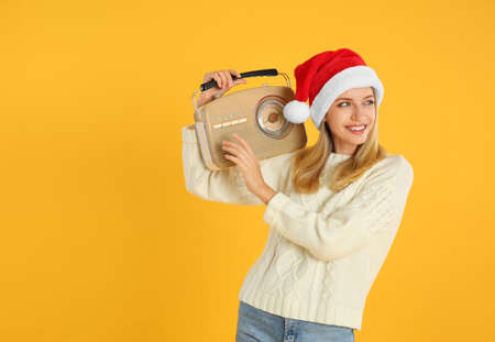 Happy woman with vintage radio on yellow background, space for text. Christmas music