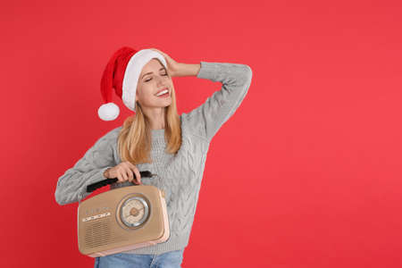 Happy woman with vintage radio on red background, space for text. Christmas music