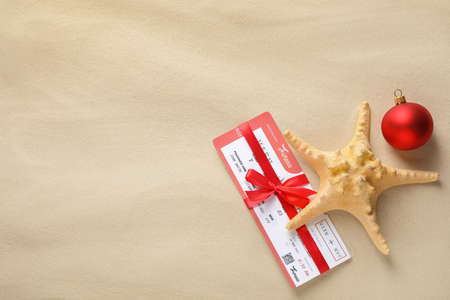 Airline ticket with red bow, starfish, festive ball and space for text on sand, flat lay. Christmas vacation Reklamní fotografie