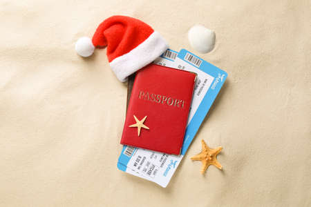 Passport with tickets and Santa hat, seashell, starfish on sand, flat lay. Christmas vacation