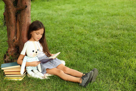 Cute little girl with toy reading book on green grass near tree in park