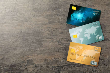 Credit cards on gray table, flat lay. Space for text