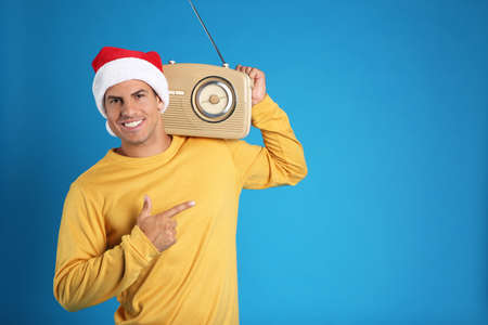 Happy man with vintage radio on blue background, space for text. Christmas music
