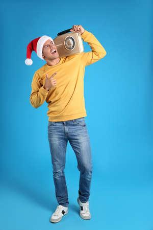 Emotional man with vintage radio on blue background. Christmas music