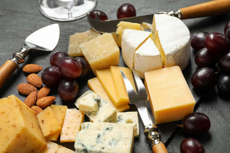 Cheese platter with specialized knives and fork on black table, closeup view