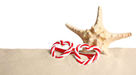 Beautiful starfish and candy cane party sunglasses on sand against white background. Christmas vacation