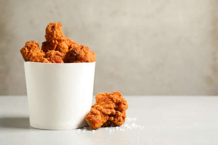 Tasty deep fried chicken pieces on white table. Space for text