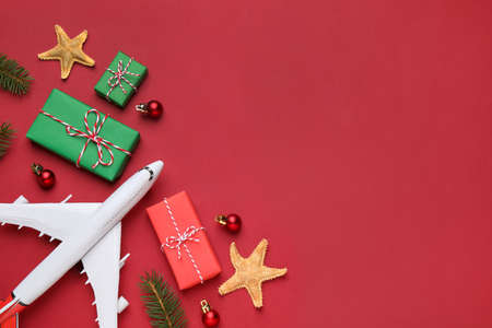 Flat lay composition with toy airplane, gift boxes and space for text on red background. Christmas vacation