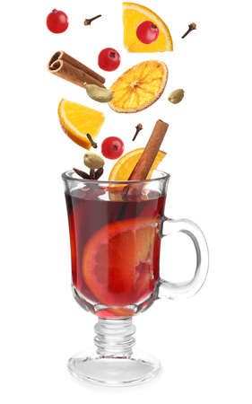 Cut orange, cranberries and different spices falling into glass cup of mulled wine on white background