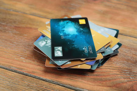 Many different credit cards on wooden table