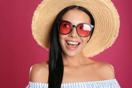 Beautiful woman wearing sunglasses on pink background, closeup
