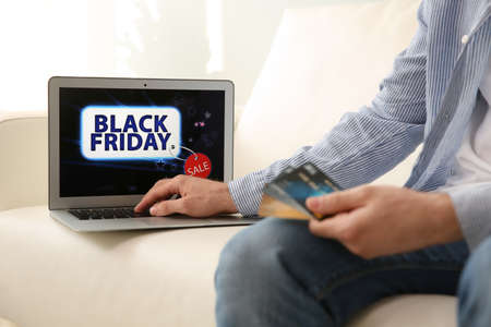 Man shopping online using laptop at home, closeup. Black Friday Sale