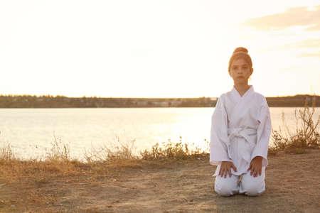 Cute little girl in kimono meditating near river at sunset. Karate practicing