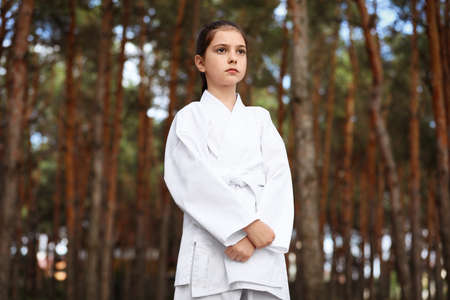 Cute little girl in kimono in forest. Karate practicing