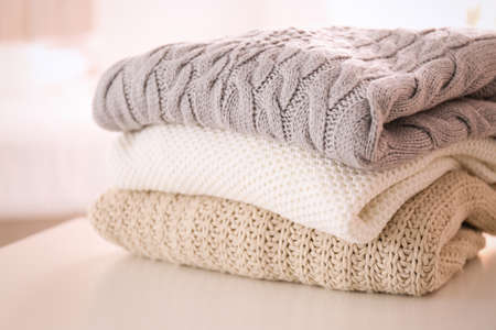 Stack of folded warm sweaters on white table indoors, closeup