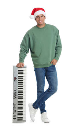 Man in Santa hat with synthesizer on white background. Christmas music Stock Photo