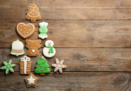 Christmas tree shape made of delicious gingerbread cookies on wooden table, flat lay. Space for text