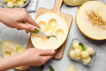 Woman making melon balls at gray table, top view Stock Photo