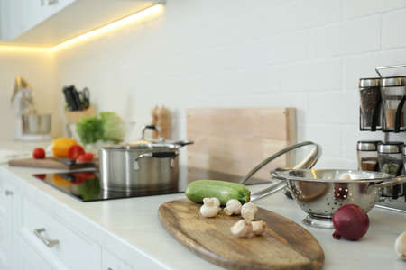 Fresh vegetables and mushrooms on white countertop in modern kitchen. Space for text Stock Photo