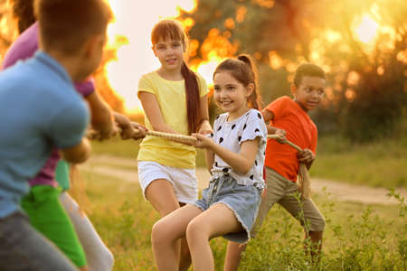 Cute little children playing tug of war game outdoors at sunset