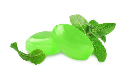 Mint hard candies and green leaves on white background